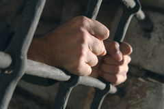 Behind bars. Hands grabbing prison bars Stock Photos