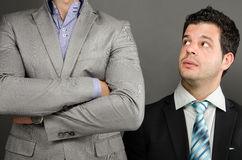 Behind the Big Man. Image of a young business man looking up at boss / colleague Stock Image