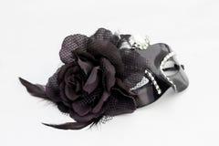 Behind the black mask. Black carnival mask on white background Royalty Free Stock Photo