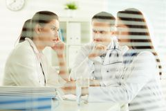 Behind the blinds. Unhappy female patient sitting in the doctor�s office, practitioners taking care of her Stock Photo
