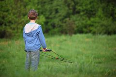 Behind boy ready to kite fly on meadow. Summer stock photography