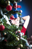 Behind Christmas tree. A young woman sleeping behind a decorated Christmas tree during the festival Royalty Free Stock Photos