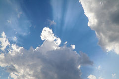 From Behind the Clouds. A photograph of rays of sunshine appearing from behind dark clouds Royalty Free Stock Image