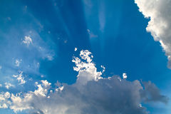 From Behind the Clouds. A photograph of rays of sunshine appearing from behind dark clouds Stock Photo