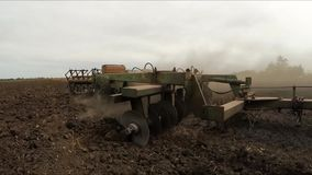 Behind the combine moves the trailer plowing field. Slow motion. Behind the combine moves the trailer lifting pieces of soil and dust behind it. Slow motion stock video