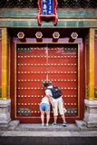 A couple peeking through the small opening in a door at the Forbidden City in Beijing China royalty free stock photography