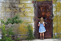 That is behind the door?. Little girl looking thru a hole to see what is on the other side of the door Royalty Free Stock Images
