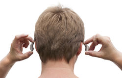 Behind-the-ear hearing aid putting on. Back view of a deaf man's head and hands putting on his behind-the-ear hearing aid royalty free stock images