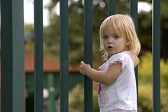 Behind the fence. Little blonde girl behind the fence looking back at the camera. Room for your text stock photos