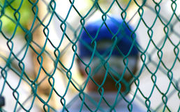 Behind the fence. Blur image of and old men behide a blue fence Royalty Free Stock Photo