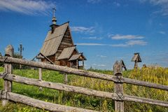 Behind the fence - An old wooden chapel in a village cemetery. Kizhi Island, Onega Lake, Karelia. Russia royalty free stock image