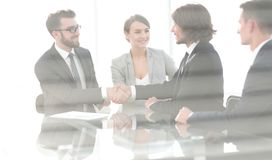 From behind the glass.handshake of business partners Royalty Free Stock Photos