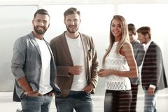 Three young employees of the company standing in the office royalty free stock photography