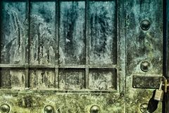 Behind The Green Door. Corroded and crusted metal door held shut by a padlock Royalty Free Stock Photo