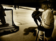 Behind the hockey net. Hockey players behind the hockey net. Photograph is processed with a grungy, gritty, worn look to evoke an old-time hockey atmosphere stock images