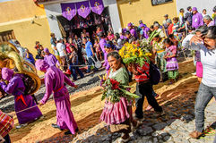 Behind Lent procession, Antigua, Guatemala. Antigua, Guatemala - Mar 1, 2015: Tail end of Lent procession walks over remains of dyed sawdust carpet in Spanish stock photos