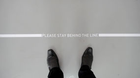 Behind the line. The sign of Please stay behind the line stock photography