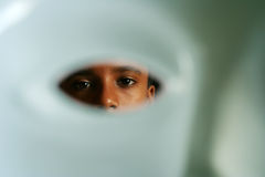 Behind the Mask. Boy looking through the mask stock photography