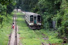 Behind of Myanmarese lady villager walking on the railroad tracks. Parallel with another rail, the train is running. stock photos