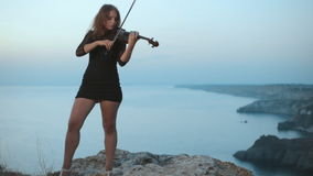 Behind playing violinist is incredibly beautiful. View on the sea coast stock footage