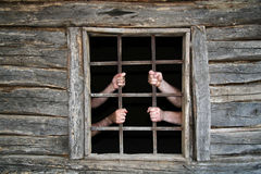 Behind Prison Bars. Men hands behind prison bars in old cottage royalty free stock photography