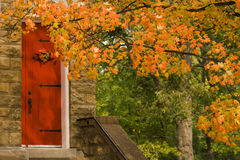 Behind The Red Door. This is a red door with black wrought iron hinges on a church in Harstelle Alabama USA. The fall leaves are a beautiful shade of orange Royalty Free Stock Photography