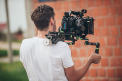 Behind the scene. Cameraman shooting film scene with his camera. Behind the scene. Cameraman shooting the film scene with his camera on outdoor location Royalty Free Stock Image