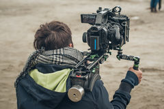 Behind the scene. Cameraman shooting film scene with his camera. Behind the scene. Cameraman shooting the film scene with his camera on outdoor location Royalty Free Stock Images
