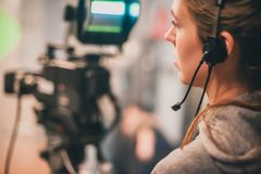 Behind the scene. Female cameraman shooting film scene with came. Behind the scene. Female cameraman shooting the film scene with camera in film studio Stock Image