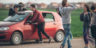 Behind scene improvisation. Film crew team pushing car with came Royalty Free Stock Photography