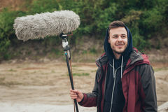 Behind the scene. Sound boom operator hold microphone fisher out Stock Photography