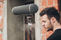 Behind the scene. Sound boom operator hold microphone fisher out Royalty Free Stock Photo