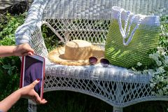 Woman`s hands with red tablet try to take a photo of composition of knitted green bag, straw hat and sun glasses on white  wicker royalty free stock images