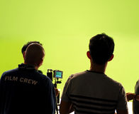 Behind the scenes of making video production. Behind the scenes of making video movie or film production and camera set and crew team shooting in a big green Royalty Free Stock Photo