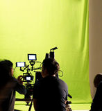 Behind the scenes of making video production. Behind the scenes of making video movie or film production and camera set and crew team shooting in a big green Royalty Free Stock Images