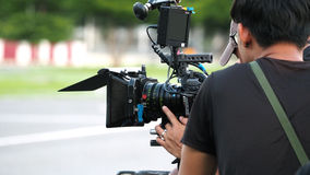 Behind the scenes of movie shooting or video production. Behind the scenes of movie shooting or video production and film crew team with camera equipment at Stock Photography