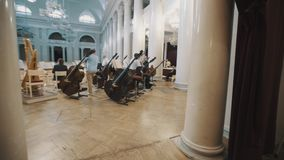 Behind the scenes musicians preparing for concert on scene of vast concert hall stock footage