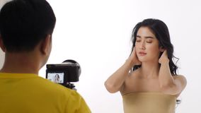 Behind the scenes shot of beautiful young asian woman model being recorded on a video camera. stock footage