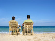 Behind sitting couple on beach 2 Stock Photos
