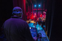 Behind sound man with musicians in background playing. Sound man working controls while the band plays in the distance under multi color lighting Stock Photo