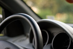 Behind the weel. Car interior detail, shallow depth of field with focus on the steering wheel Stock Images