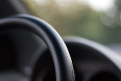 Behind the wheel 2. Car interior detail, shallow depth of field with focus on the steering wheel Royalty Free Stock Image