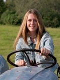 Behind the Wheel. A beautiful farmer's daughter behind the wheel of an antique tractor stock images