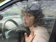 Behind the wheel. A woman in a car behind the wheel. Window covered with rain drops stock photography