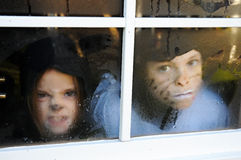 Behind the window. Two children, dressed in halloween bat costumes making faces behind a window Stock Photo