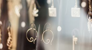 Behind the window of a store, a display of earring fancy Stock Photo