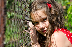 Behind a wire fence. Girl behind a wire fence Royalty Free Stock Photography