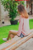 Behind a woman sitting on a long wooden chair. stock photo