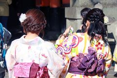 Behind of women in Kimono dress and deep pink sash in Japanese temple. Kimono is a long, loose robe with wide sleeves and tied with a sash, originally worn as Royalty Free Stock Images