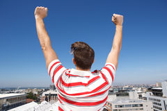 Behind of young man with arms raised outdoors Stock Image